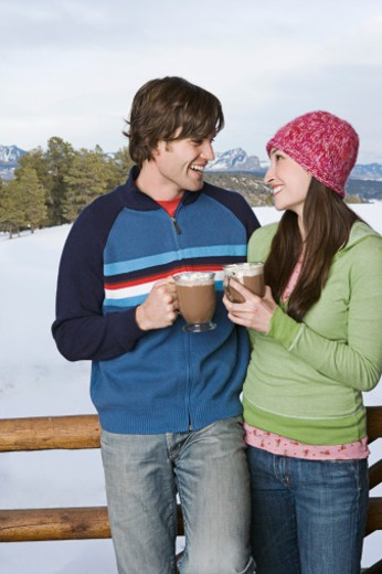 Stock Photo: 1555R-314222 Couple drinking hot cocoa on deck