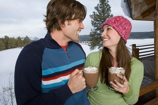 Couple enjoying hot cocoa together on deck : Stock Photo