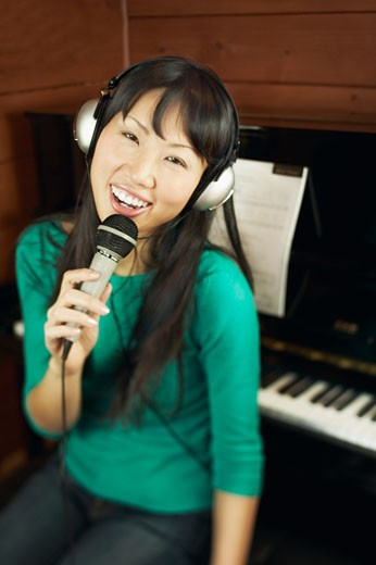 Woman with headphones singing : Stock Photo