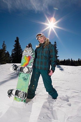 Stock Photo: 1555R-314666 Woman posing with snowboard