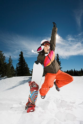 Woman jumping with snowboard : Stock Photo