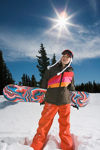 Stock Photo: 1555R-314671 Woman standing with snowboard