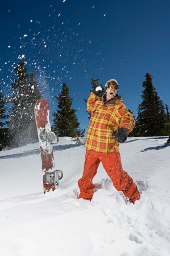 Snowboarder throwing snowball : Stock Photo