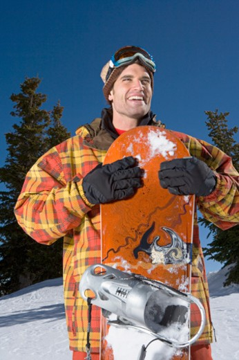 Stock Photo: 1555R-314681 Smiling man with snowboard