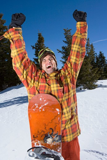 Stock Photo: 1555R-314684 Excited man with snowboard
