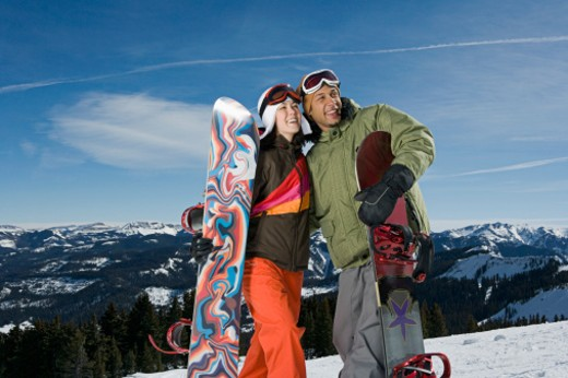 Stock Photo: 1555R-314686 Couple with snowboards looking away