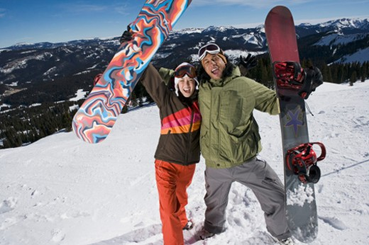 Triumphant snowboarding couple : Stock Photo