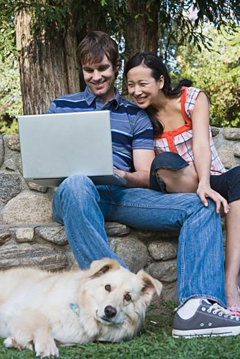 Couple with laptop computer and dog : Stock Photo