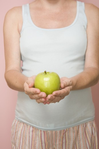 Stock Photo: 1555R-315704 Torso of pregnant woman holding green apple