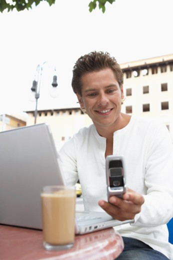 Stock Photo: 1555R-315808 Man at cafe with laptop computer and cell phone