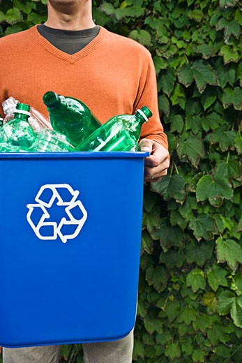 Stock Photo: 1555R-316324 Man carrying recycling bin