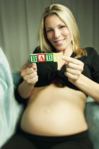 Stock Photo: 1555R-316381 Pregnant woman holding blocks