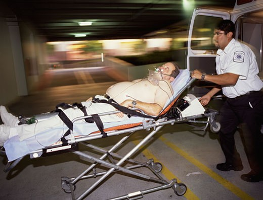 Emergency medical worker pushing patient on gurney : Stock Photo