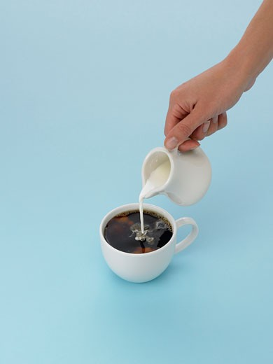 Hand pouring cream into coffee : Stock Photo