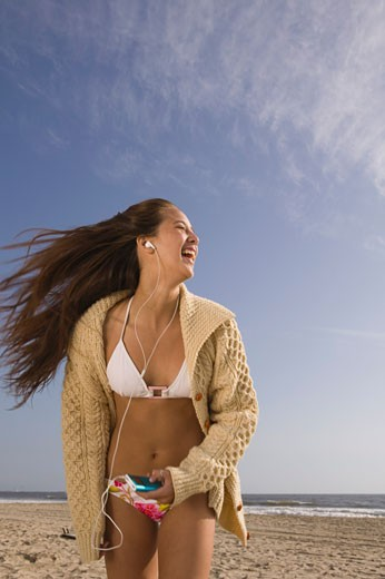 Teenage girl listening to headphones and dancing on beach : Stock Photo