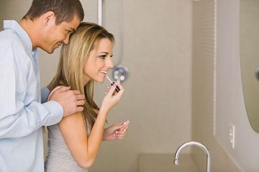 Man touching woman applying makeup : Stock Photo