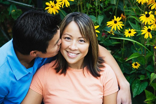 Man kissing woman on cheek : Stock Photo