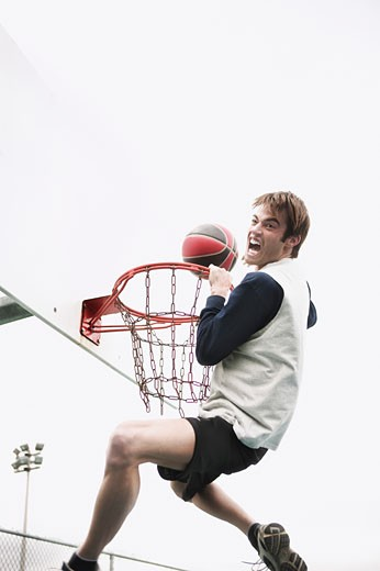Stock Photo: 1555R-321430 Screaming man hanging on basketball hoop