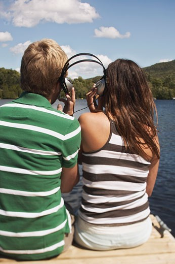 Teenage couple on dock sharing headphones : Stock Photo