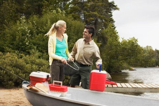 Couple with boat and fishing supplies : Stock Photo