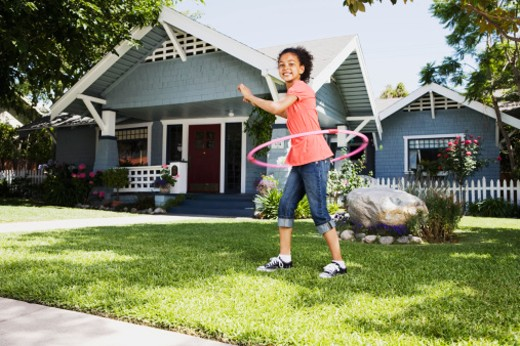 Girl with plastic ring toy on front lawn of house : Stock Photo