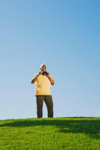 Senior man with binoculars : Stock Photo