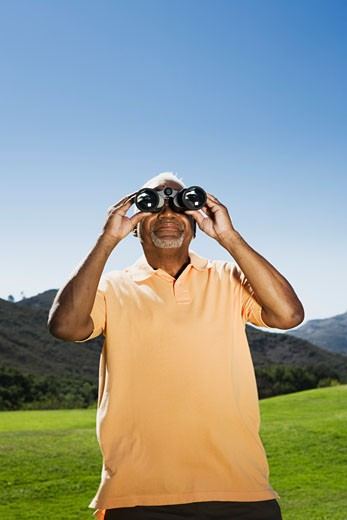 Senior man with binoculars : Stock Photo