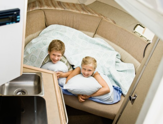Boy and girl lying down in boat cabin : Stock Photo