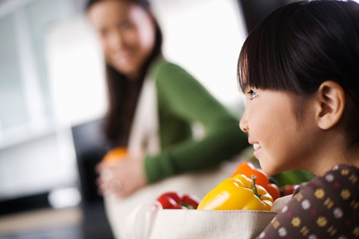 Side view of girl with bag of produce : Stock Photo
