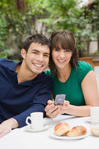 Smiling couple at cafe with cell phone : Stock Photo