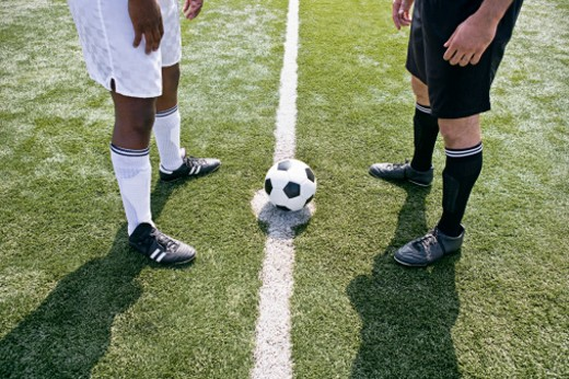Opposing soccer players at half-way line : Stock Photo
