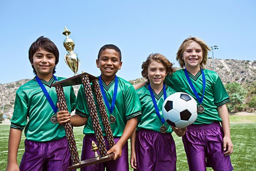 Boys' soccer team holding trophy : Stock Photo