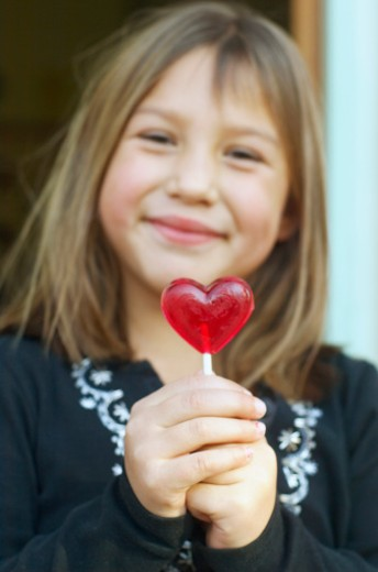 Stock Photo: 1555R-324257 Smiling girl with heart shaped lollipop