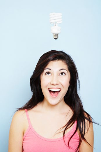 Woman having idea with lightbulb : Stock Photo