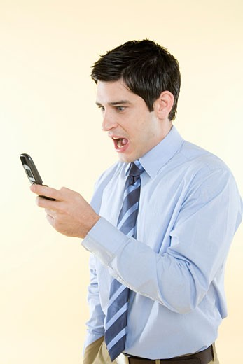 Stock Photo: 1555R-325315 Businessman reacting to text message
