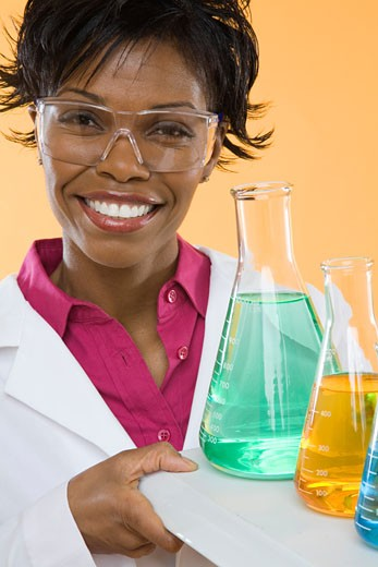 Scientist with flasks and safety glasses : Stock Photo