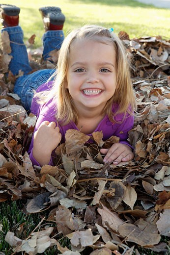 Smiling girl in pile of leafs : Stock Photo