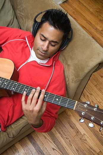 Man with headphones playing guitar : Stock Photo