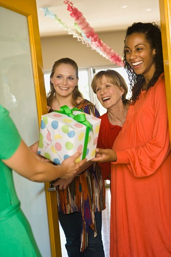 Women in doorway with gift : Stock Photo