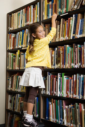 Stock Photo: 1555R-326043 Girl reaching for book on bookshelf