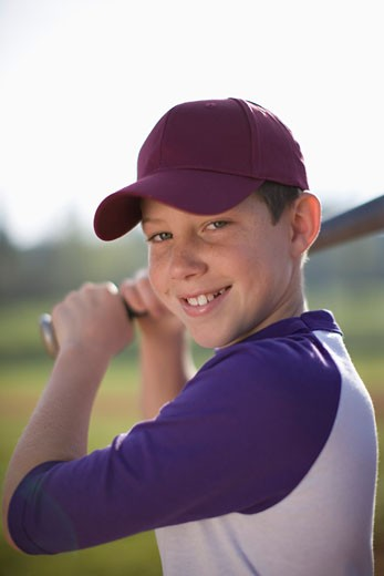 Portrait of boy in baseball uniform on field : Stock Photo
