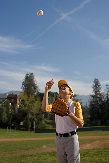 Portrait of boy with baseball mitt throwing ball : Stock Photo