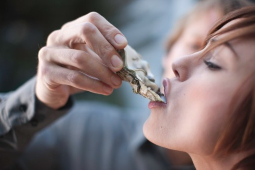 Close-up of young woman being fed an oyster by man. : Stock Photo