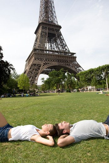 Stock Photo: 1555R-330430 Couple lying on grass, Eiffel Tower in background