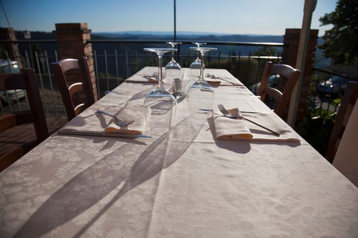 long evening shadows on a dinner table on the terrace of a restaurant : Stock Photo