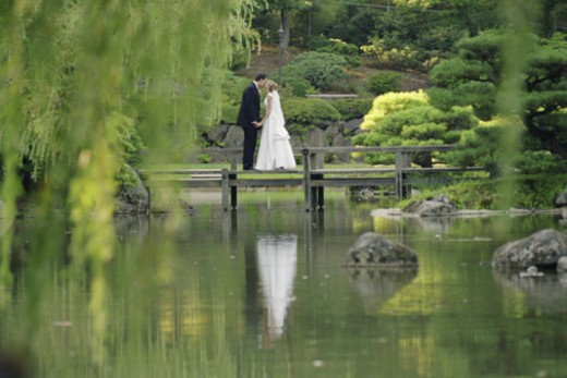 Newlyweds kissing by pond in Japanese garden : Stock Photo
