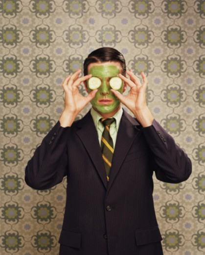 Man holding cucumber slices over eyes : Stock Photo