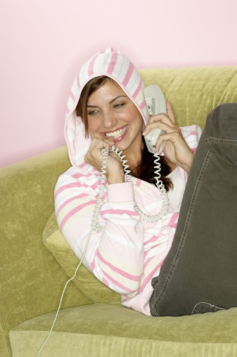 Stock Photo: 1555R-332119 Woman lounging on sofa on telephone