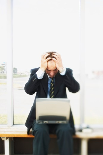 Stock Photo: 1555R-332335 Stressed man with laptop