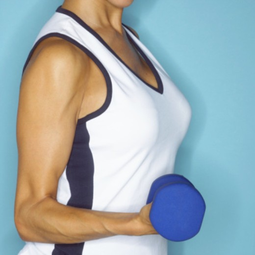 Woman lifting dumbbell : Stock Photo